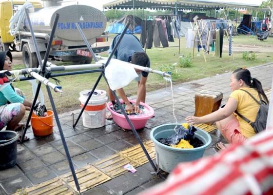 Nusabali.com - mencuci-pakaian-di-lapangan-terbuka