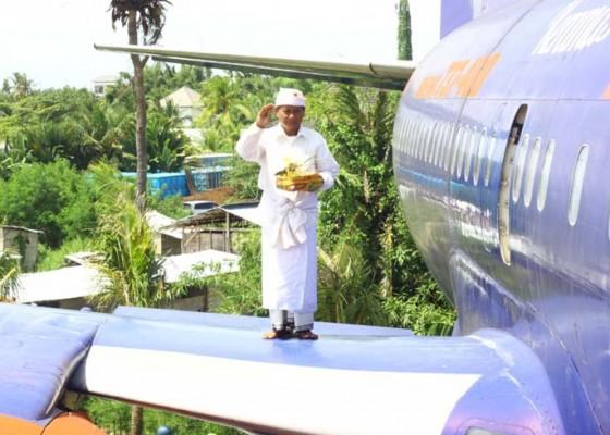 Nusabali.com - nganteb-banten-pamangku-naik-sayap-pesawat