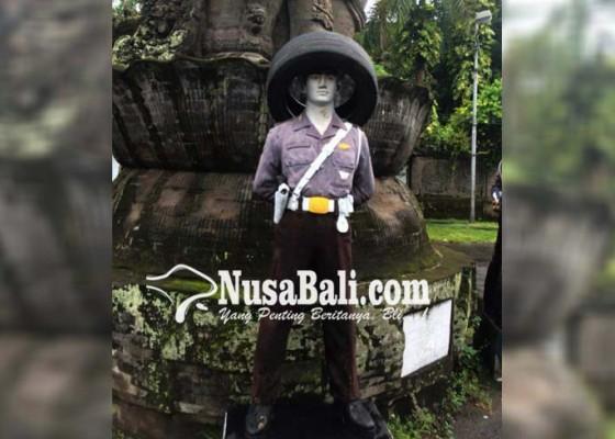 Nusabali.com - patung-polisi-dipasangi-ban-mobil