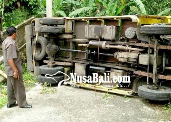 Nusabali.com - tak-kuat-nanjak-truk-muat-kayu-terguling