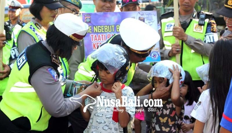 www.nusabali.com-polres-buleleng-bagi-helm-gratis-untuk-anak-anak