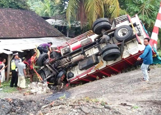 Nusabali.com - truk-terguling-kaki-sopir-terjepit