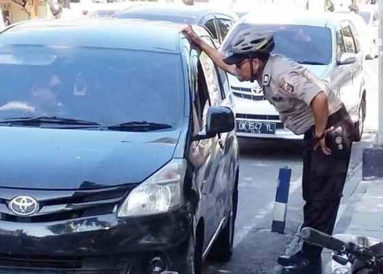 Nusabali.com - polisi-tegur-pemarkir-mobil-di-jalan-poppies