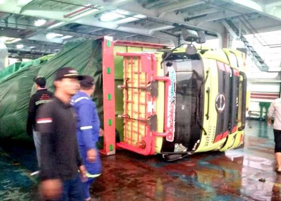 Nusabali.com - cuaca-buruk-truk-muat-pakan-terguling-di-dalam-kapal