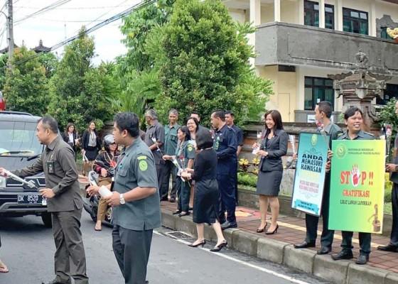 Nusabali.com - pn-bangli-bagikan-bunga-dan-stiker-anti-korupsi