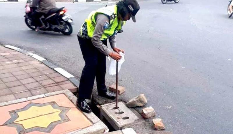 www.nusabali.com-polisi-pasang-batu-di-trotoar-berlubang