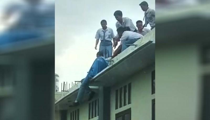 www.nusabali.com-naik-ke-atap-gedung-berlantai-dua-kemudian-diselamatkan-rekannya