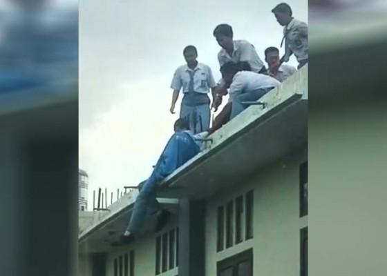 Nusabali.com - naik-ke-atap-gedung-berlantai-dua-kemudian-diselamatkan-rekannya