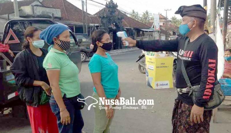 www.nusabali.com-pecalang-cek-suhu-tubuh-pengunjung-pasar-ulakan
