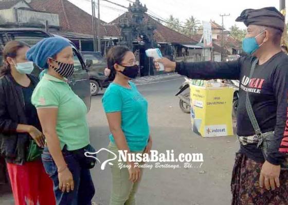 Nusabali.com - pecalang-cek-suhu-tubuh-pengunjung-pasar-ulakan