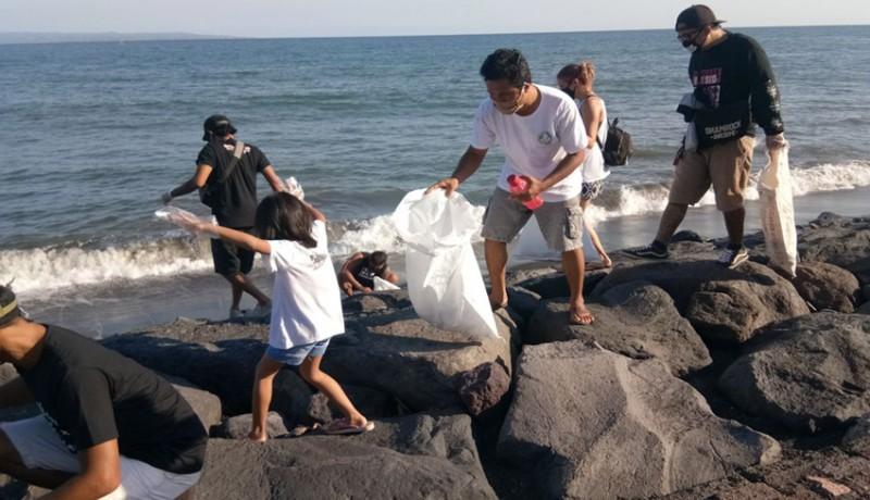 www.nusabali.com-solidaritas-gianyar-bersama-jrx-bersih-pantai-dan-bagi-pangan-di-pantai-lebih